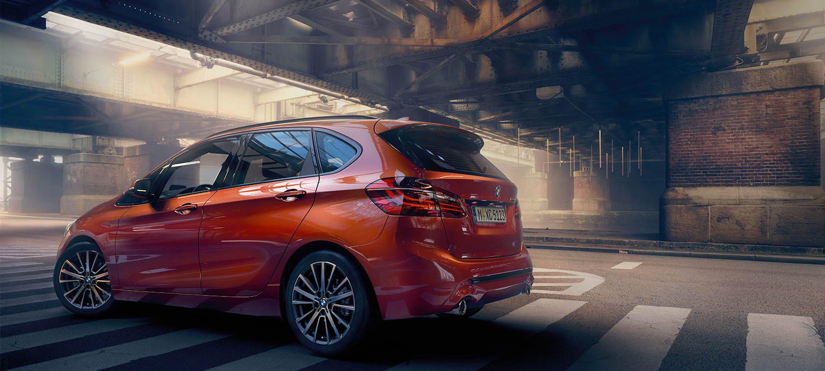 BMW 2-serie Active Tourer F45 Facelift 2018 Sunset Orange Metallic set fra siden i en hal
